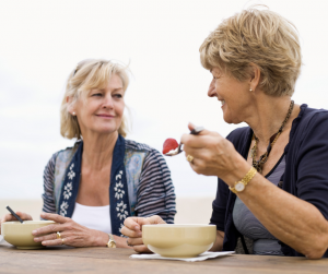 Two older women sharing a meal and talking