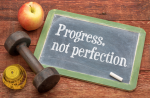 "image of a blackboard showing the phrase ""progress not perfection"""
